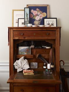A French secretary in the bedroom holds important papers and displays favorite small paintings and a sturdy dried leaf.