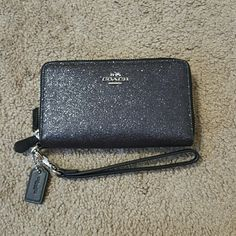 NWT Black Glitter Double Zip Coach Wristlet NWT Black Glitter Double Zip Coach Wristlet Super cute Wristlet with plenty of card pockets a coin case and pockets for paper money! Silver accents amd silver exposed zippers please note as I tried to show in the 3rd pic there is some slight variation (lines) on the back very hard to see I can only assume it was manufactured that way as I didn't notice until I was photographing it. It is so cute pictures don't do it justice Coach Bags Clutches…
