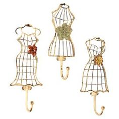 """Set of three metal wall hooks with a dress form design.Product: 3 Piece wall hook setConstruction Material: MetalColor: Cream, red, yellow and greenFeatures: Distressed finishDimensions: 10.5"""" H x 5"""" W x 2.5"""" D each"""