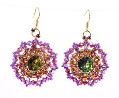 Treat yourself to something special to spark your day with these shimmering earrings! Swarovski rivoli crystal in vitrail green with pink hues, faceted to lure maximum light, is framed with gold seed beads and crystal copper Czech superduo beads. Swarovski crystal, seed beads and double hole glass beads in gold, fuschia and hues of pink form two additional mandala circles edged with tiny pink seed beads.