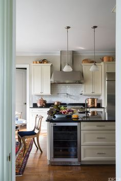 The kitchen's wine refrigerator and vent hood are by GE Monogram; the Regency-style mahogany dining chairs are from the 1940s, and the collection of copper cookware includes antique and vintage pieces.