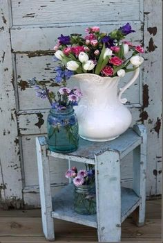 Love the old white chippy door in background ...the plant stand and the white pitcher of posies!!!!!!!!!!!!!.