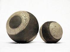 ...aus 2 schweren Keramik-Kugeln aus grobschamottiertem Ton, im Raku-Verfahren teilglasiert und anschließend im Rauchbrand durch Sauerstoffentzug g...