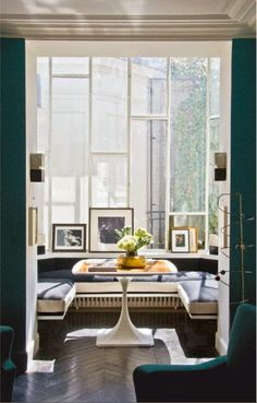 Glass enclosed sunroom, table, leaning artwork