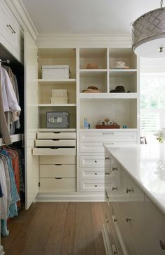 Gorgeous walk-in closet with secret cabinet which opens to built in, pull out drawers and closet safe beside built-in dresser below open shelving with double stacked clothes rails to the left across from a large closet island with drawer storage, accented with nickel pulls, below a white counter lit by a nickel lattice drum pendant with diffuser.