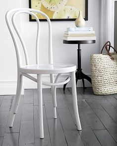 In 1859, Michael Thonet introduced the concept of bending wood with steam to design the iconic bentwood chair. Our Vienna White Wood dining chair is produced in one of the original Thonet factories in Europe. This timeless, curvy classic is both incredibly strong and light, making it a popular choice for bistros and cafes. A white lacquer finish gives it crisp versatility.