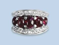A RETRO RUBY AND DIAMOND DRESS RING   Composed of a line of graduated cabochon rubies flanked by arched lines of brilliant-cut diamonds, circa 1950