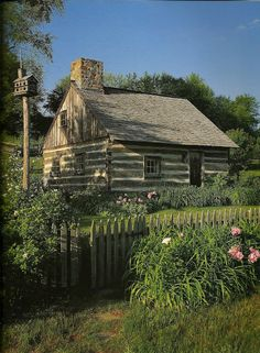 Adorable cabin & garden with a picket fence.