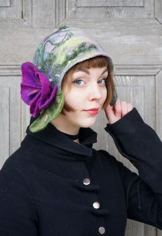 Beautiful and unique felted cloche hat, retro style hat with purple violet flower and green leaves, purple, gray and green. Its made nuno felted technique with silk fabric and merino wool, decorated with wool fleeces, silk fibers and pieces of silk fabric. Flower isnt sewn, it was felted together with hat. Warm, light and elegant. Head circumference -ca 56 cm ( 22 inches )