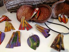 A wonderful display of bright enamel earrings resting on local seed pods and logs at Crest Gallery.