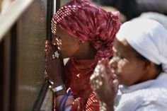 Ethiopian jews women observe through a gate men performing the Cohanim prayer (priest's blessing) during the Pesach (Passover) holiday at the Western Wall in the Old City of Jerusalem on April 17. Thousands of Jews make the pilgrimage to Jerusalem during the eight-day Pesach holiday, which commemorates the Israelites' exodus from slavery in Egypt some 3,500 years ago and their plight by refraining from eating leavened food products.