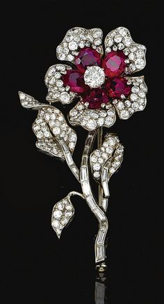 RUBY AND DIAMOND BROOCH, VAN CLEEF & ARPELS, 1952  Designed as a flower, the petals set with oval rubies and brilliant-cut diamonds, the stem set with baguette stones, to brilliant-cut diamond set leaves, mounted in platinum,   signed Van Cleef & Arpels and numbered, French assay and maker's marks, case.