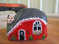 little red house painted on a rock