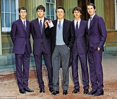 Bryan receiving his CBE at the Palace with sons (from left) Merlin, Isaac, Tara…