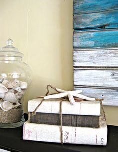 Easy and cheap decor item: old books. You can paint the covers to match your decor. Simple palet painted in background is beachy and whimsical.