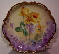Beautiful Limoges Charger Decorated with Vibrant Hand Painted Yellow Roses and Lavender Background with Bold Gild Rococo Border. 13-1/4 Diameter.