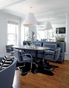 """Designer Todd Haley hung an oversize lampshade from CB2 for """"tension and excitement"""" in a sophisticated Lincoln Park dining area and balanced it with upholstery in a calming lavender hue. """"I showed the client only one fabric,"""" Haley says of the Knoll textile he used for the chairs and the banquette."""