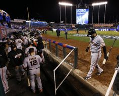 San Francisco Giants Gregor Blanco, right, walks back to the dugout after being struck out by Kansas City Royals pitcher Tim Collins to end Game 6 of baseball's World Series Tuesday, Oct. 28, 2014, in Kansas City, Mo. The Royals defeated the Giants 10-0 to tie the series at 3-3. (AP Photo/Matt Slocum)