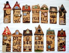 """Ouiji board houses---""""I'm making a whole street of houses...I bought this Ouija board for $1 at my beloved Re-Use centre and went to town. I chopped it into 13 rectangles and then embellished each one with a roof, numbered it with the appropriate stamp and decorated them with buttons and other goodies."""""""