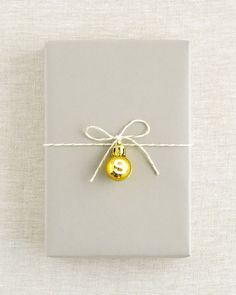 The simplest idea to dress up a gift, but so wonderfully effective! Buy mini baubles and string onto your wrapping.. Simple, classic and festive!