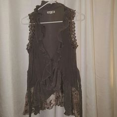 Beautiful casual summer shirt Grey sleeveless with beautiful lace on bottom. Has a tie for front and back. You can dress this with anything. mine Tops Camisoles