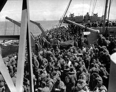 """Dans un convoi un navire transport de troupes militarisé APA, voir les deux postes de DCA. Le pont est rempli de soldats américains avec leurs gilets de sauvetage, on remarque quelques membres de l'US Navy, voir les coiffures ; des """" hats """" pour l'USN et des calots pour l'US Army. On distingue quelques insignes de bras de la 5th US ID la """"red diamond division"""".  Cette division débarque à Utah Beach."""