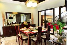 In the center of the dining area is a square eight-seater dining table on a cream-colored area rug. Behind it is a large wall mirror hanging above a wooden buffet table. The area is illuminated with a droplight that has a tropical feel. �