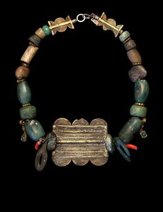 19th c. green serpentine is joined with ancient stone beads, Hittite amulets and a 19th c. Nigerian bronze pendant. Small coral and brass objects highlight the green stones. CL001 SOLD