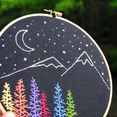 In this one-of-a-kind embroidery hoop, colorful pine trees in rainbow hues are stitched in the foreground against tall mountain peaks. The scenery is complete with the crescent moon and stars in the night sky. This modern nature scene would look great by itself or fit right in with the artwork in a gallery wall.  Details: - 7 wooden embroidery hoop frame (7 inches / 17.78 CM) - Securely covered backing - Lightweight & easy to hang - Ready to ship!  Switch up the artwork in your space with…