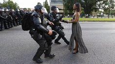 Eine friedliche, schwarze Frau im Sommerkleid wird von Polizisten in schwerer Schutzausrüstung festgenommen. Ein Fotograf nahm die Szene in Baton Rouge auf – sie versinnbildlicht die gesamte Debatte über Polizeigewalt in den USA. Im Netz finden sich weitere erschütternde Videos.