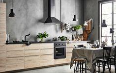 Et kjøkken med en rad benkeskap med fronter i ask mot en betonggrå vegg.