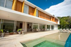 Galeria da Arquitetura | Casa Canto da Lagoa - Em concreto armado, a fachada recebe brises de madeira