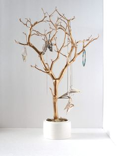 Spray paint a branch, anchor in small pot with river rocks. Jewelry holder