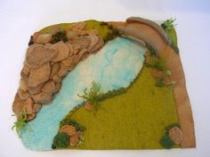 Story mat made from felt showing a birdge corssing a river,on oneside rocky terrain,the other a lush grass.