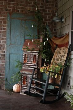 Love the look of this Prim Porch...old door, log cabin, & front porch rocker.