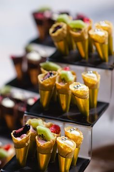 Desserts in waffle cones are topped with fresh fruits and edible silver pearls.