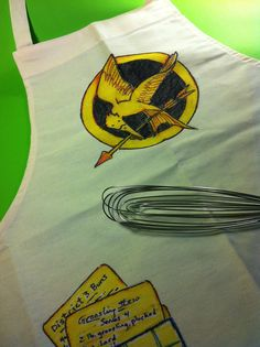 """A painted canvas apron project makes a great activity for a """"Hunger Games"""" party. (And you can tuck Groosling Stew recipes in the pocket! Theme Parties, Party Themes, Party Ideas, Gift Ideas, Hunger Games Party, Painted Canvas, Pooh Bear, Catching Fire, Party Planning"""