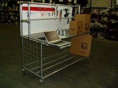 A warehouse workstation cart that has roof for laptop computer, packing materials and tools.