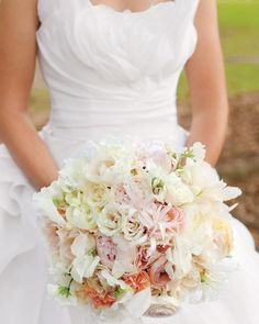 A large bouquet of sweet peas, roses, peonies, and white feathers complements her custom-made dress.