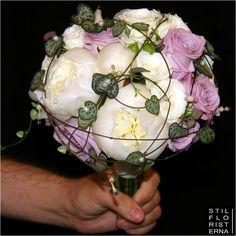 Klassiskt elegant brudbukett handbunden med vita pioner och lavendelrosor.