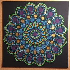 Hand painted 12x12-inch peacock inspired dot mandala painting on flat panel canvas. Painted with black background and dotted using colors found in peacock feathers (i.e. blues, purple, green, and metallic gold). The outer ring of the dot mandala was designed to duplicate the actual