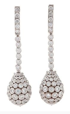 Cartier Diamond and Platinum Earrings A pair of French platinum and diamond drop ear pendants by Cartier. The earrings feature 230 round-cut diamonds with an approximate total weight of 13.00 carats. The bezel set diamond encrusted cones are suspended by an articulated bezel set line of diamonds which extend up the ea