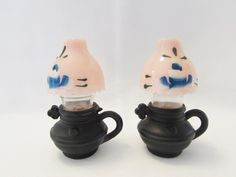 "Cast Iron Oil Lamp Shakers.  This set of salt and pepper shakers are oil lamps.  The base of the lamps appear to be cast iron.  The tops are plastic.  There is a blue floral pattern painted on the pink shades.  The shakers are approx. 3"" tall.  They are in good condition.  There is wear and scratching to the plastic."