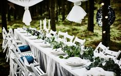 A forest wedding dining table with a white tabletop, lacy curtains as a tablecloth, white folding chairs, white tableware and a table runner centerpiece made of greenery