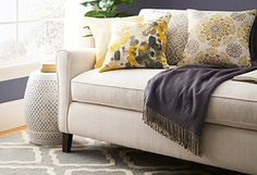 Welcome the Sun - Rays of yellow and gold warm up this collection's cool grey palette, offering a classic color pairing with a bright and cheery feel. Mix and match woven poufs, chic rugs, painterly pillows and more to let the sunshine in.