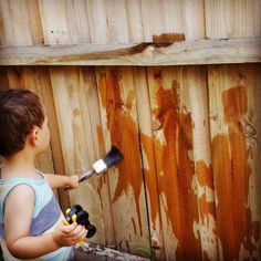 """Keep your toddler busy by letting them """"paint"""" the fence with water. 