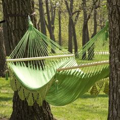 A lovely crocheted hammock in light spring green suspended between two sturdy, mature trees.