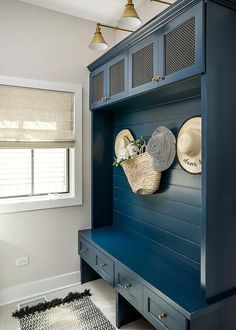 Blue built-in mudroom wall displays shiplap trim over a bench with lower storage drawers accented by brass hardware.