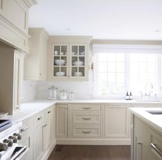 """serious dream kitchen that we designed for our #pennstoneproject this year. Inspired by the timeless cabinetry of the UK (aren't we always?) we treated the cabinetry like furniture, mixed glass doors with closed storage, and used honed white marble on every surface (cabinet color is Sherwin Williams """"Relaxed Khaki""""). #highstreethomedesign #myhighstreethome"""