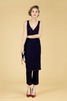 Karin Rocke      AVA   Das Kleid Ava aus reiner Wolle mit V-Ausschnitt hat einen geraden schmalen Schnitt. Das Kleid ist in einem Ajourmuster gestrickt und am Saum farblich abgesetzt und der Ausschnitt ist durch ein Ringelmuster farblich betont.